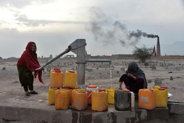 Женщина наполняет канистры питьевой водой в Джелалабаде