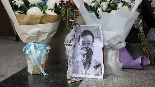 Цветы в память о враче Ли Вэньляне у входа в Центральную больницу Уханя