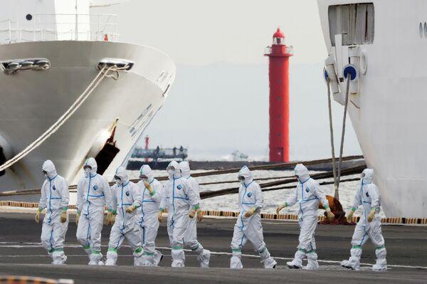 Люди в защитных костюмах поднимаются на борт круизного судна Diamond Princess в Йокогаме