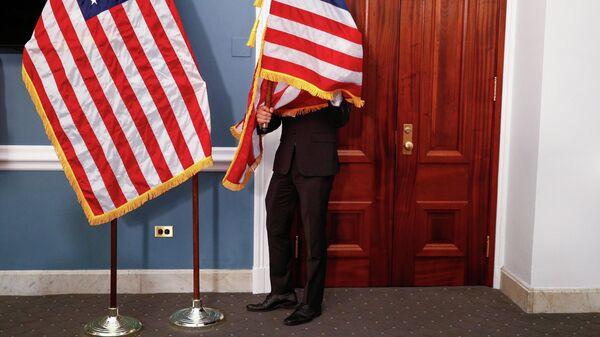 Сотрудник с американскими флагами в здании Капитолия США в Вашингтоне
