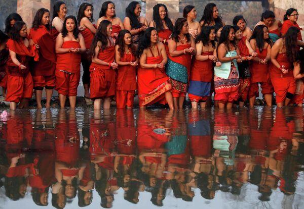 Женщины стоя на берегу реки Хануманте в Бхактапуре, Непал