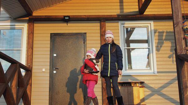 Дочери Екатерины и Алексея Богачевых на крыльце нового дома с котом