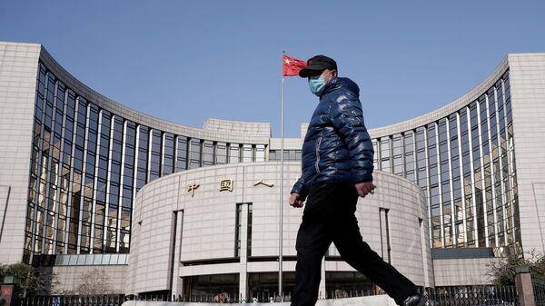 Мужчина в защитной маске проходит мимо штаб-квартиры Народного банка Китая в Пекине