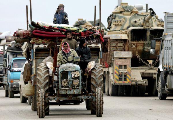 Покинувшие свои дома сирийцы и колонна турецкой военной техники в Хазано, недалеко от Идлиба