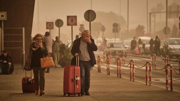 Пассажиры прикрывают в облаке красной пыли в аэропорту Санта-Крус-де-Тенерифе, Испания
