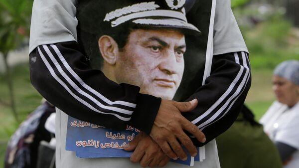 Мужчина держит фотографию экс-президента Египта Хосни Мубарака