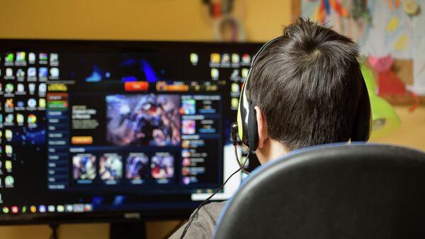 Подросток играет за компьютером