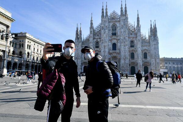 Туристы фотографируются на фоне собора в Милане