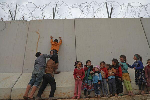 Сирийские дети пытаются перебраться через турецкую пограничную стену в северо-западной провинции Сирии