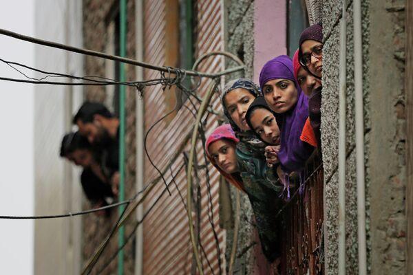Индийские мусульманки выглядывают в окно во время патрулирования сотрудниками службы безопасности улицы в Нью-Дели
