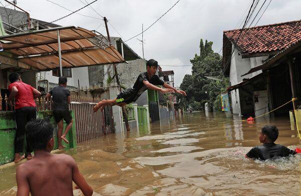 Индонезийская молодежь развлекается во время наводнения в окрестностях Джакарты
