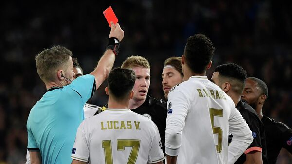 Real Madrid's Spanish defender Sergio Ramos (C) is handed a red card by Italian referee Daniele Orsato during the UEFA Champions League round of 16 first-leg football match between Real Madrid CF and Manchester City at the Santiago Bernabeu stadium in Madrid on February 26, 2020. (Photo by JAVIER SORIANO / AFP)