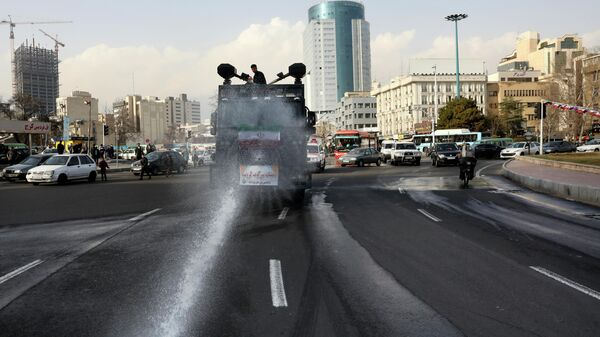 Полицейский автомобиль распыляет дезинфицирующее средство в Тегеране