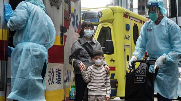 Женщина с ребенком в защитных масках рядом с автомобилем скорой помощи в Гонконге