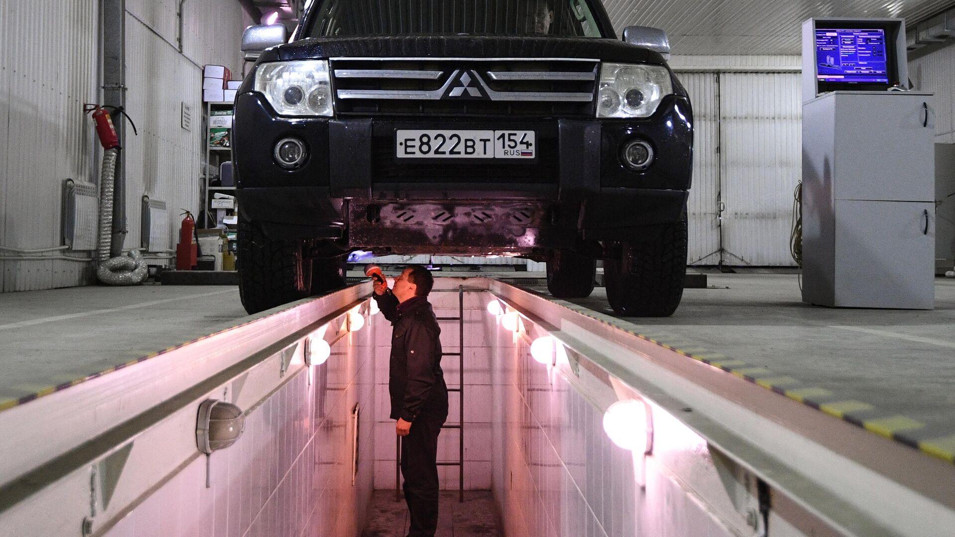 Технический эксперт проводит осмотр автомобиля на пункте техосмотра в Новосибирске - РИА Новости, 1920, 30.04.2021