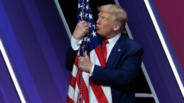 Президент США Дональд Трамп целует американский флаг после выступления на Конференции консервативных политических действий