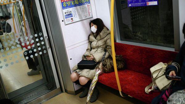 Женщина в медицинской маске  в поезде в Японии
