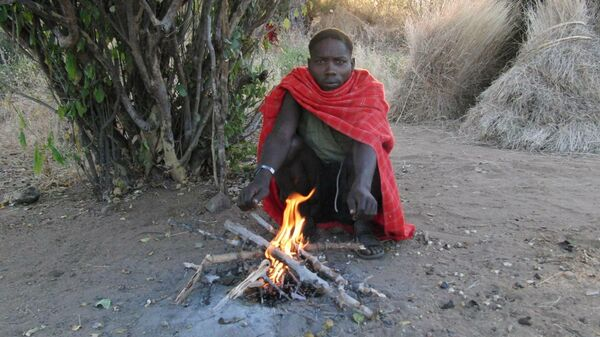 Мужчина племени хадза (Танзания), сидящий на корточках