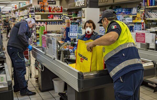 Сотрудники социальной службы покупают продукты людям пожилого возраста для предотвращения распространения инфекции