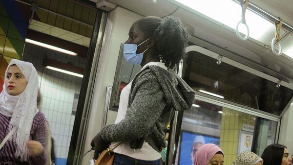 Женщина в защитной маске во время поездки на метро по линии Шубра-эль-Хайма  на окраине Каира, Египет