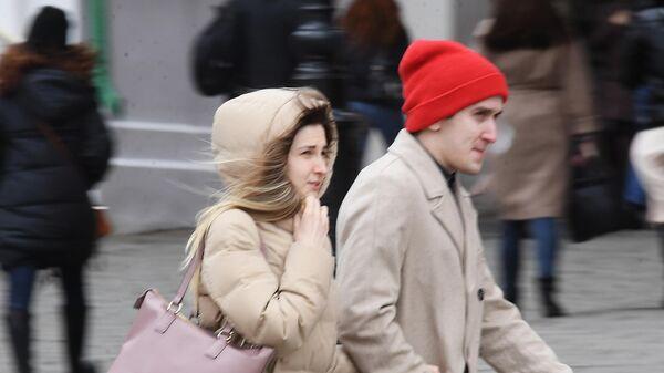 Люди идут по улице под порывами ветра в Москве