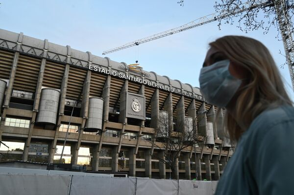 Девушка в защитной маске у стадиона Сантьяго Бернабеу в Мадриде