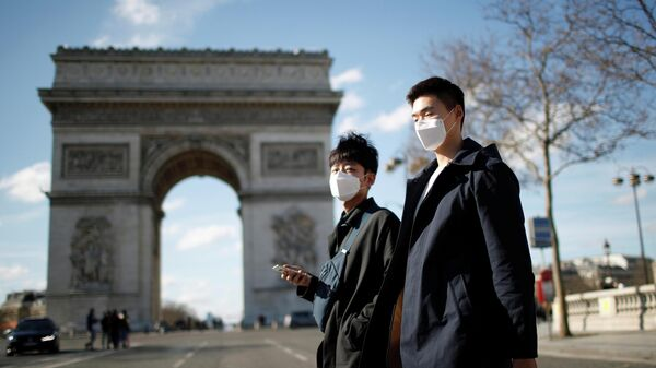 Люди в защитных масках у Триумфальной арки в Париже