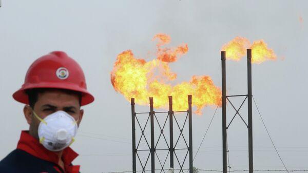 Рабочий в защитной маске на нефтяном месторождении в Ираке