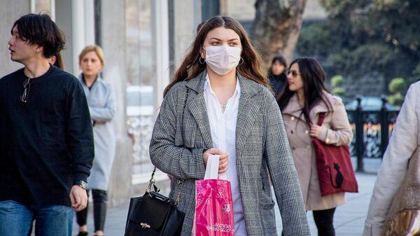 Девушка идет по улице Тбилиси в медицинской маске