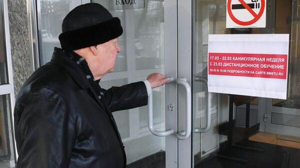 Мужчина на входе в здание Московского Государственного Технического Университета имени Н. Э. Баумана в Москве