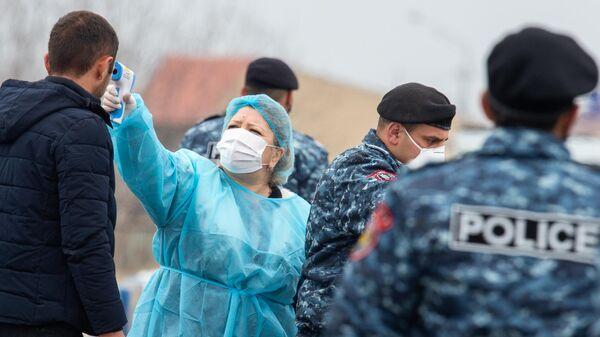 Медицинский работник проверяет температуру у прохожего в Ереване