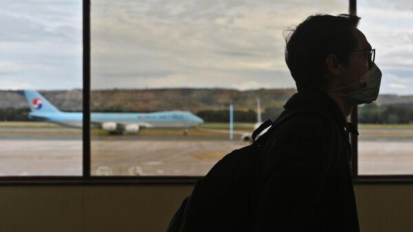 Мужчина в защитной маске в аэропорту