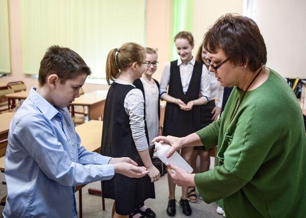 Сотрудница школы обрабатывает ученикам руки дезинфицирующим раствором в одной из школ Москвы