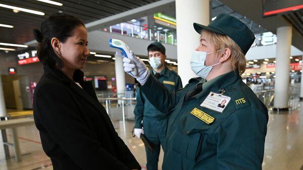 Сотрудница службы транспортной безопасности измеряет температуру у одного из пассажиров на железнодорожном вокзале Адлера
