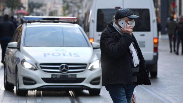 Мужчина в медицинской маске на одной из улиц Стамбула