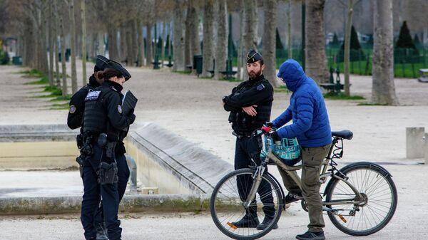 Полицейские проверяют документы велосипедиста на Марсовом поле в Париже
