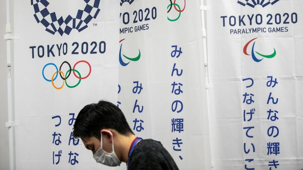 A reporter wearing a face mask stands next to the banners of the Tokyo Olympic and Paralympic Games during a Tokyo 2020 press conference about the spread of the new coronavirus in Tokyo on March 17, 2020. - Tokyo 2020 organisers said on March 17 they were scaling back certain parts of the Olympic torch relay due to the coronavirus but that spectators would be allowed to watch from the roadside. (Photo by Behrouz MEHRI / AFP)