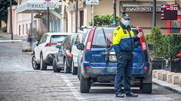 Полицейский в защитной маске на улице Тбилиси
