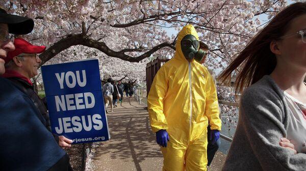 Молодой человек в защитном костюме и противогазе в Вашингтоне
