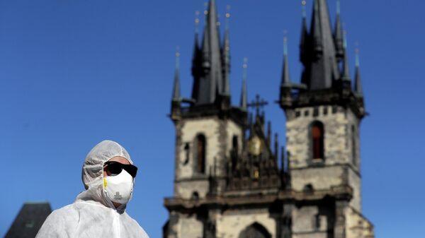 Мужчина в защитном костюме на Староместской площади в Праге