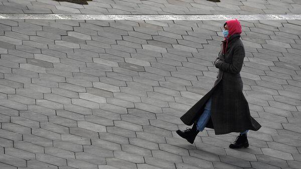 Женщина в медицинской маске на одной из улиц Москвы
