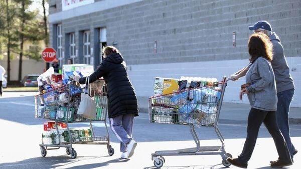 Покупатели выходят из магазина в Мелвилле, штат Нью-Йорк