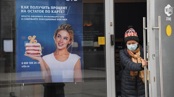 Посетитель выходит из отделения банка ВТБ на одной из улиц в Москве