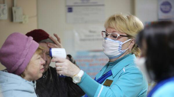 Сотрудница поликлиники  измеряет температуру посетительницы в связи с угрозой распространения коронавируса