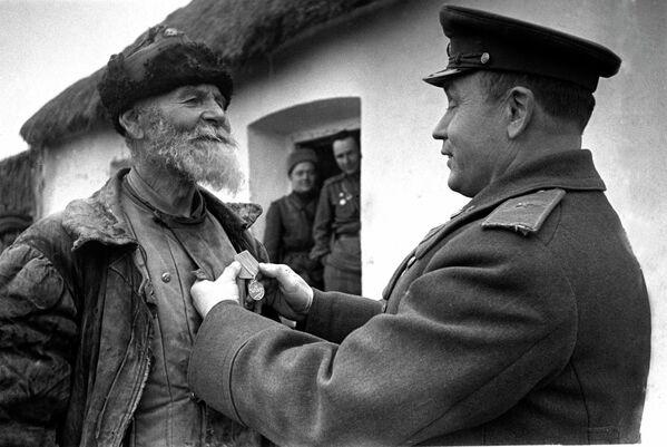 Командир дивизиона награждает колхозника Помкина за подвиг