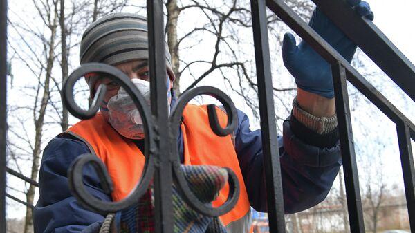Сотрудник коммунальной службы проводит санитарную обработку парадной на одной из улиц Санкт-Петербурга