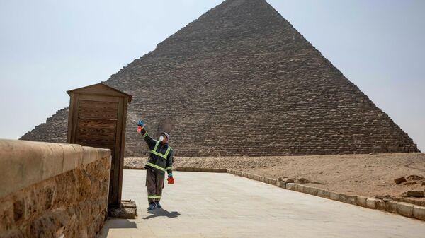 Рабочий во время дезинфекции комплекса пирамид в Гизе