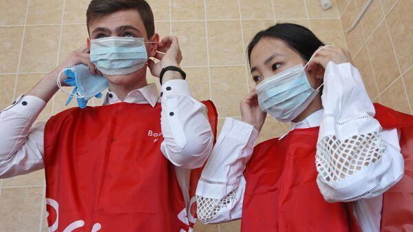 Волонтеры надевают медицинские маски перед тем, как пойти в магазин в Барнауле