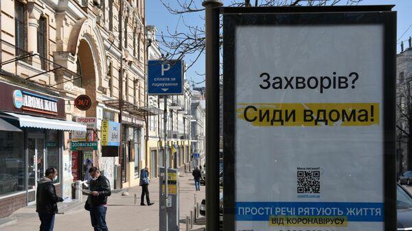Информационный плакат, призывающий оставаться дома, на одной из улиц в Киеве