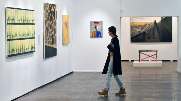 Посетительница в одном из залов Московского музея современного искусства, где выставлены лоты аукциона Vladey